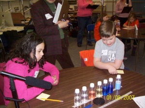 Students observing the properites of a liquid in bottles before investigating them as a data collector looks on.